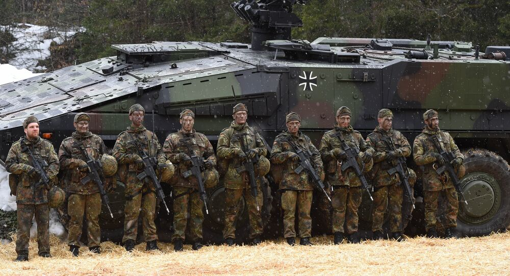Mountain infantry soldiers stand in front of a troops transporter Boxer after an exercise of the mountain infantry brigade 23 of the German Bundeswehr near the Bavarian village Bad Reichenhall, southern Germany, on March 23, 2016