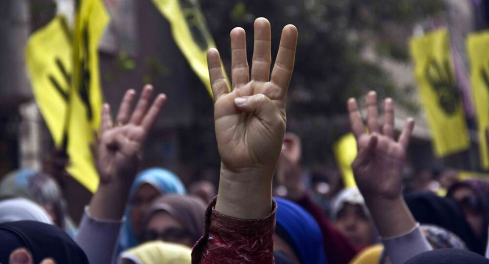 Pro-Brotherhood protesters raise their hands with the Rabia gesture during a march