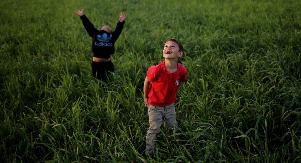 Children look to the sky as they play with a kite in a field at a makeshift camp for migrants and refugees at the Greek-Macedonian border near the village of Idomeni, Greece, April 17, 2016.