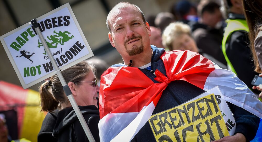 A demonstrator holds a placard reading rapefugees not welcome during a demonstration against Islamic terror organised by far-right movement Pegida Vlaanderen, on April 23, 2016, in Antwerp