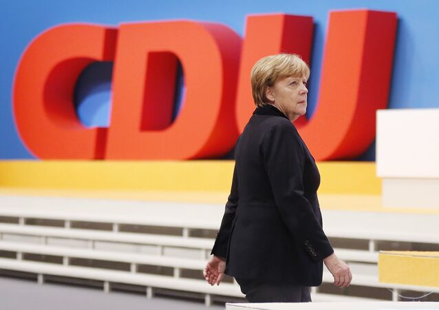 German Chancellor Angela Merkel walks past the party logo during a party convention of the Christian Democrats (CDU) in Karlsruhe, Germany, December 14, 2015.