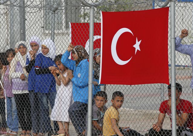 Migrants stand behind a fence at the Nizip refugee camp in Gaziantep province, southeastern Turkey, Saturday, April 23, 2016