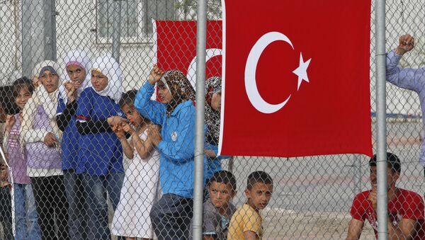 Migrants stand behind a fence at the Nizip refugee camp in Gaziantep province, southeastern Turkey, Saturday, April 23, 2016 - Sputnik International