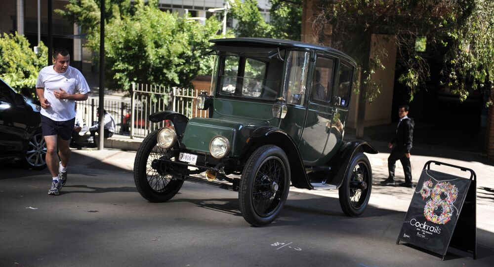 In this photograph taken on September 5, 2012, Bill Lloyd, 61, (obscured) a retired Australian mechanical engineer, patent attorney and vintage car collector sits in his 1915 Detroit electric car out of the garage in Sydney
