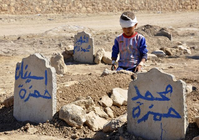 Ali Hamza, 8, sits at the graves of his brother, Mohammed, and sister Asinat, who were killed in a suicide car bomb attack in the Shiite Turkmen village of Qabak near Tal Afar. file photo