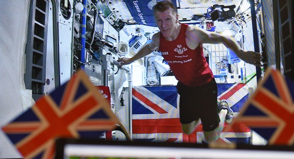 British astronaut Tim Peake is seen on a video screen transmitted from the International Space Station (ISS) at the astronaut centre of the European Space Agency ESA in Cologne, Germany, Sunday, April 24, 2016. Peake ran a 42 kilometre marathon on a tread mill in space onboard the (ISS).