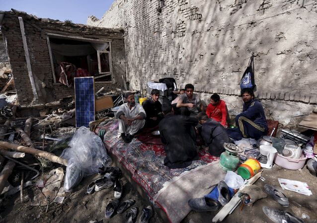 Residents have lunch inside their damaged house after yesterday's suicide car bomb attack on a government security building in Kabul, Afghanistan, April 20, 2016.