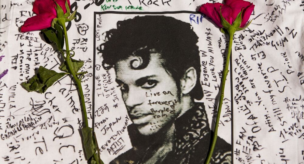 Flowers lay on a T-shirt signed by fans of singer Prince at a makeshift memorial place created outside Apollo Theater in New York.