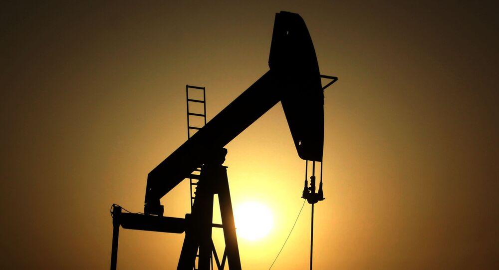 Sun sets behind an oil pump.