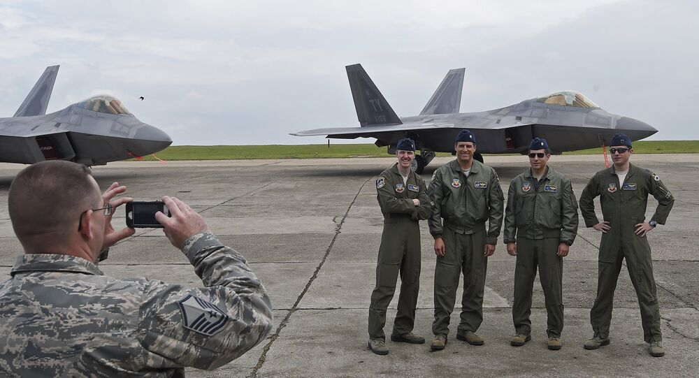 US pilots pose for a photograph in front of US F-22 Raptor fighters parked on the runway at Mihail Kogalniceanu air base in Romania April 25, 2016.