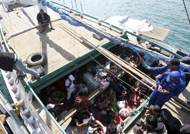 In this May 12, 2013 file photo, Iranian asylum seekers who were caught in Indonesian waters while sailing to Australia sit on a boat at Benoa port in Bali, Indonesia. Papua New Guinea's Supreme Court on Tuesday, April 26, 2016 ruled that Australia's detention of asylum seekers at a facility on the country's Manus Island is unconstitutional.