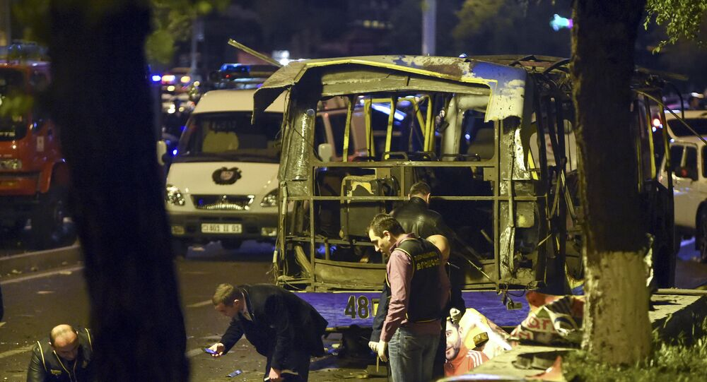 In this Monday night, April 25, 2016 photo, experts search the site of a passenger bus explosion in Halabyan street of Yerevan, Armenia.