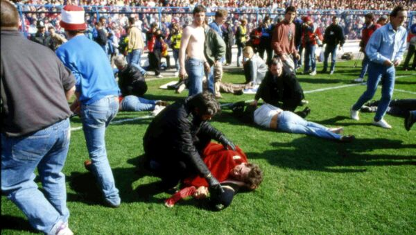 FILE - In this April 15, 1989 file photo police, stewards and supporters tend and care for wounded supporters on the field at Hillsborough Stadium, in Sheffield, England. - Sputnik International