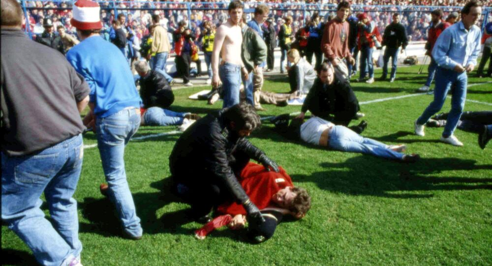 FILE - In this April 15, 1989 file photo police, stewards and supporters tend and care for wounded supporters on the field at Hillsborough Stadium, in Sheffield, England.