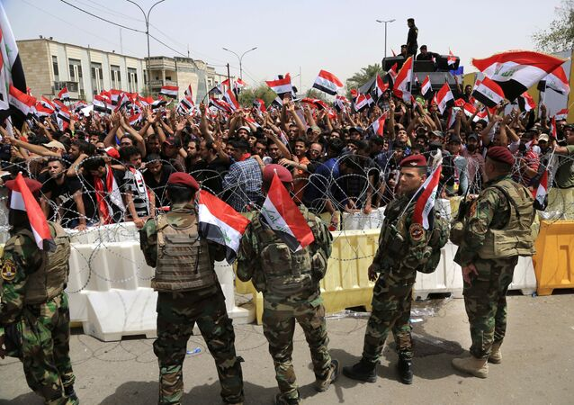 Iraqi security forces guard the heavily fortified Green Zone as followers of Iraq's influential Shiite cleric Muqtada al-Sadr wave national flags as they gather in front of the Green Zone, ahead of a scheduled parliament session to press for a vote on a new government, in Baghdad, Iraq, Tuesday, April 26, 2016.