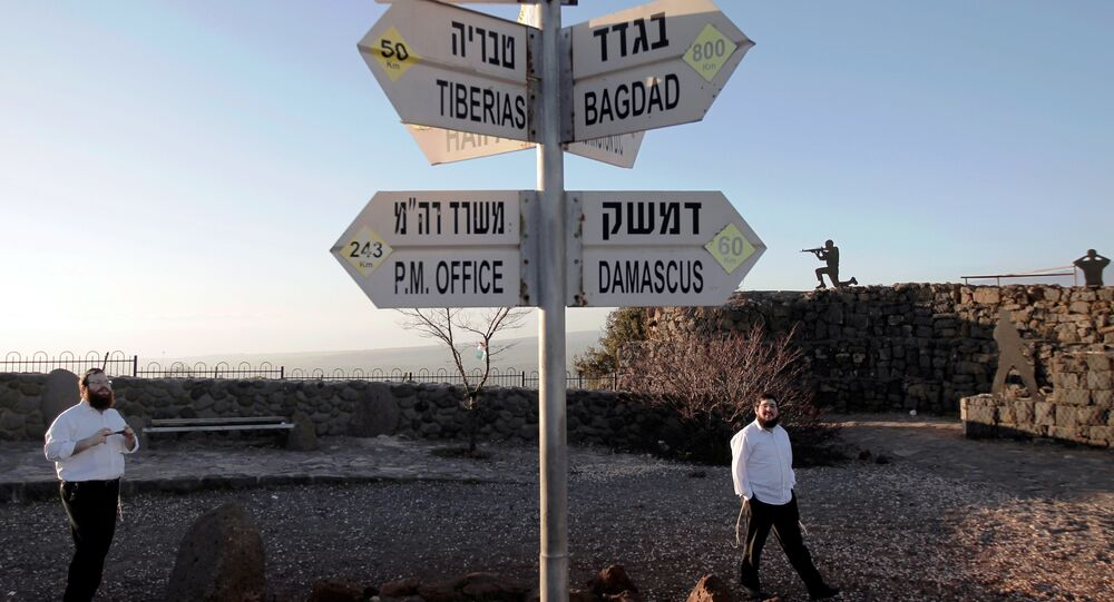 Israelis walk near a sign for tourists showing the distance to Damascus and Baghdad among other destinations at an army post on Mount Bental in the Israeli-annexed Golan Heights on March 10, 2016.
