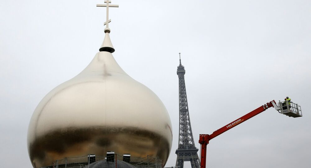 A crane transports a cross to be placed on one of the domes of the future Russian orthodox cathedral Sainte-Trinite at the Quai Branly, near the Eiffel Tower, central Paris, on March 19, 2016.