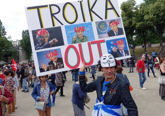 A man holds a sign that reads Troika Out as people take part in a demonstration called by associations, unions and left-wing politicians in support of both migrants and the Greek people on June 20, 2015 in Paris.
