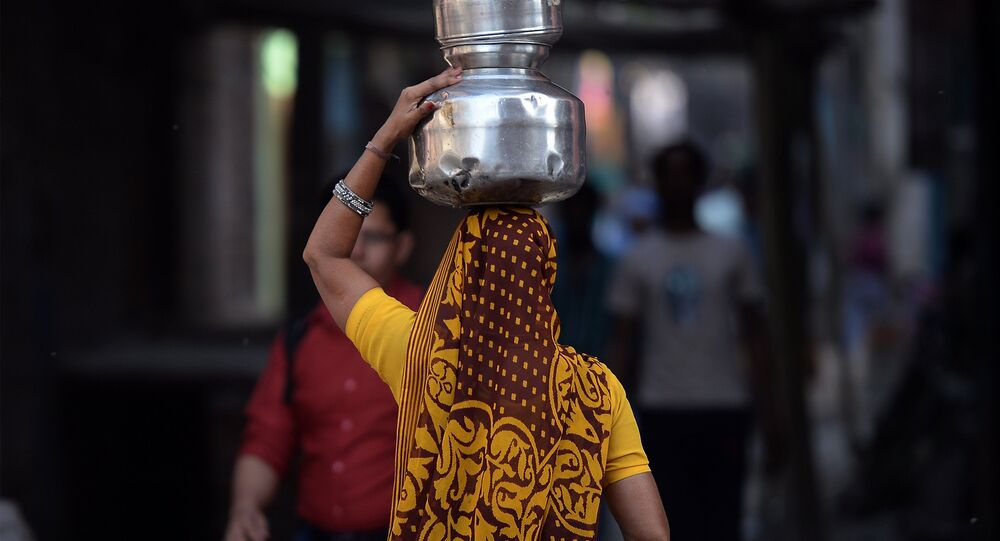 An Indian woman carries drinking water containers