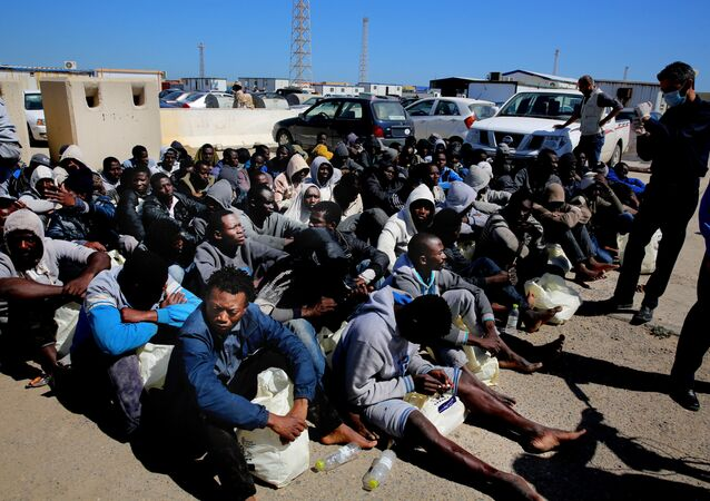 African illegal migrants wait to receive medial assistance after being rescued by coastal guards on a port in Tripoli, Libya.