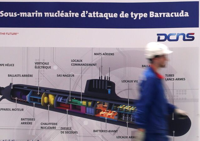 An employee walks past a poster showing a Barracuda submarine at the industrial site of the naval defence company and shipbuilder DCNS in La Montagne near Nantes, France, April 26, 2016