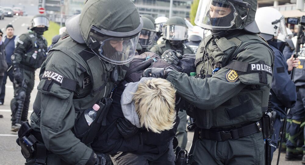 Police detain a leftist demonstrator on the occasion of a party convention of the Alternative for Germany, or AfD, in Stuttgart, Germany Saturday, April 30, 2016
