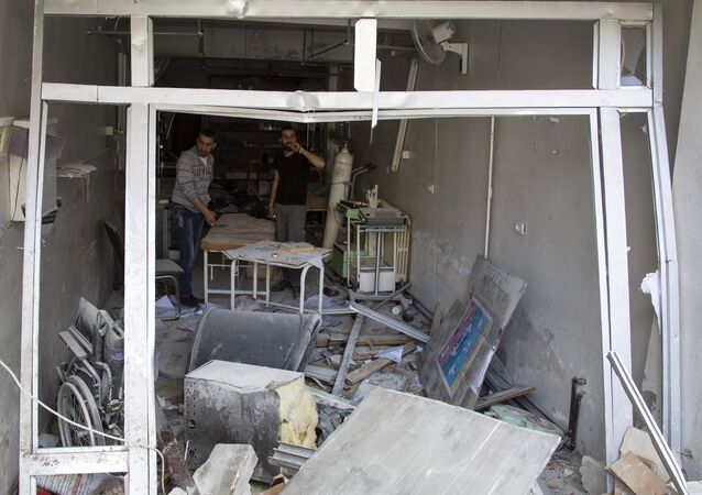 A picture taken on April 28, 2016 shows Syrian men inspecting the damage at the Al-Quds hospital building following reported airstrikes on the rebel-held neighbourhood of Sukkari in the northern city of Aleppo.