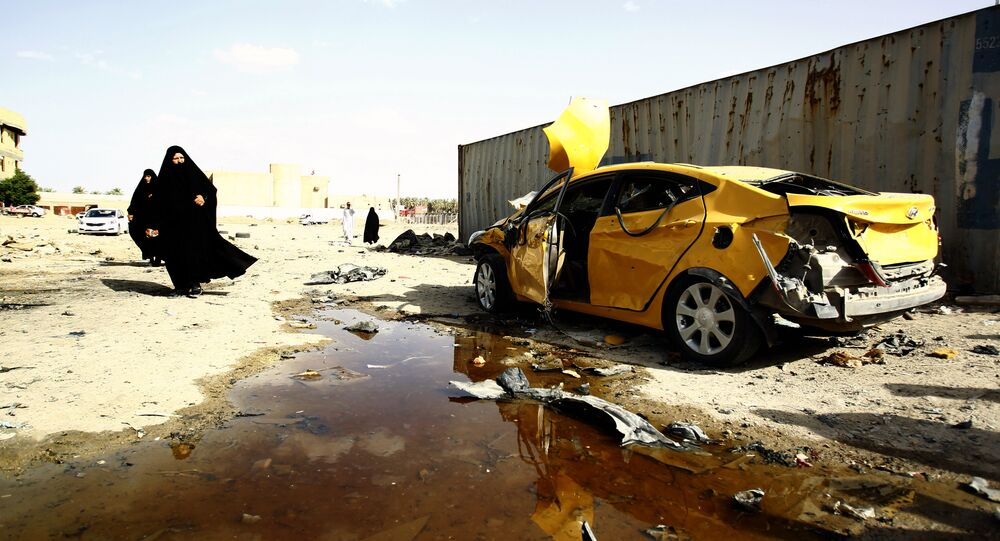 Iraqi women walk past a damaged car following a twin suicide bombing attack, claimed by the Islamic State (IS) group, in the southern Iraqi city of Samawah, situated deep in Iraq's Shiite heartland, on May 1, 2016