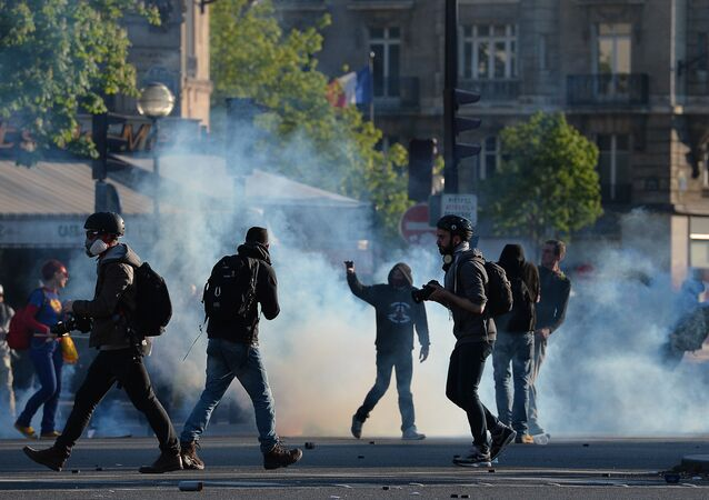 Protesters and photographers stand on the Place de la Nation during clashes with police at a traditional May Day demonstration on May 1, 2016, in Paris.