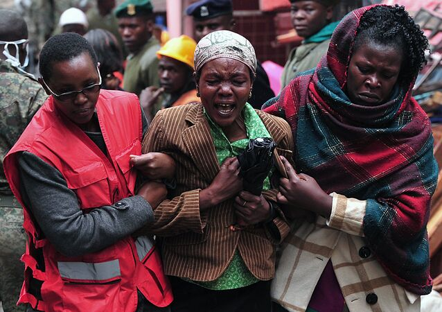 A Kenyan woman (C) mourns the loss of a relative at the site of a building collapse in Nairobi on April 30, 2016. Rescuers in the Kenyan capital made desperate efforts to free survivors including a woman and child trapped in a building that collapsed in storms that have left a total of 17 people dead.