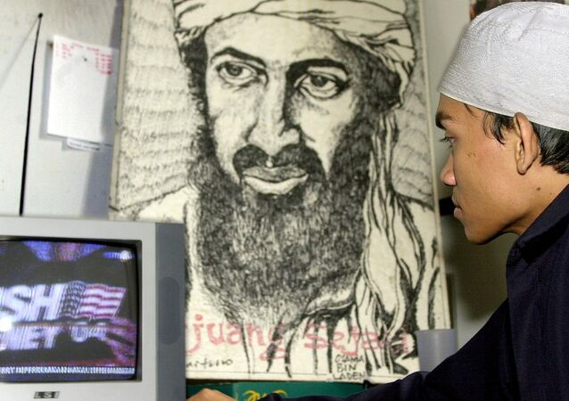 An Indonesian Muslim youth watches a television coverage of the US elections in front of a portrait of Osama bin Laden at a Islam youth movement headquarters in Jakarta, 03 November 2004