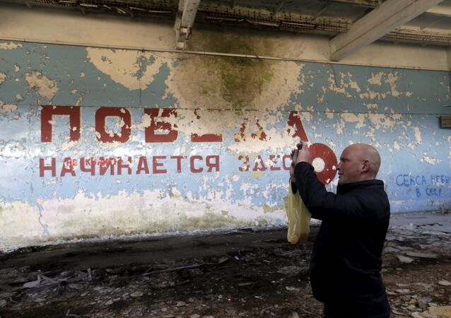 A man takes a picture inside sports hall in the ghost town of a former Soviet military radar station near Skrunda, Latvia, April 9, 2016. The words on the wall reads in Russian Victory starts here