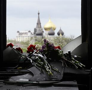 Flowers on a broken window in memory of the people killed by fire in the Trade Unions House on Odessa's Kulikovo Field Square. File photo