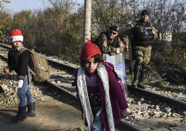 Police officers watch two children walk past as migrants and refugees cross the Greek-Macedonian border near the town of Gevgelija, Macedonia (File)