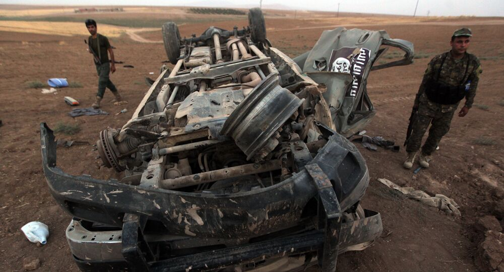 Peshmerga fighters inspect the remains of a car, bearing an image of the trademark jihadist flag, which reportedly belonged to Daesh militants after it was targeted by an American airstrike in the village of Baqufa, north of Mosul