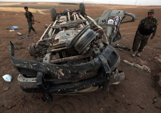 Peshmerga fighters inspect the remains of a car, bearing an image of the trademark jihadist flag, which reportedly belonged to Islamic State (IS) militants after it was targeted by an American air strike in the village of Baqufa, north of Mosul (File)