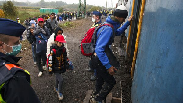 Migrants board a train after making their way through the countryside and crossing the Hungarian-Croatian border near the village of Zakany in Hungary to continue their trip to north on October 16, 2015 - Sputnik International