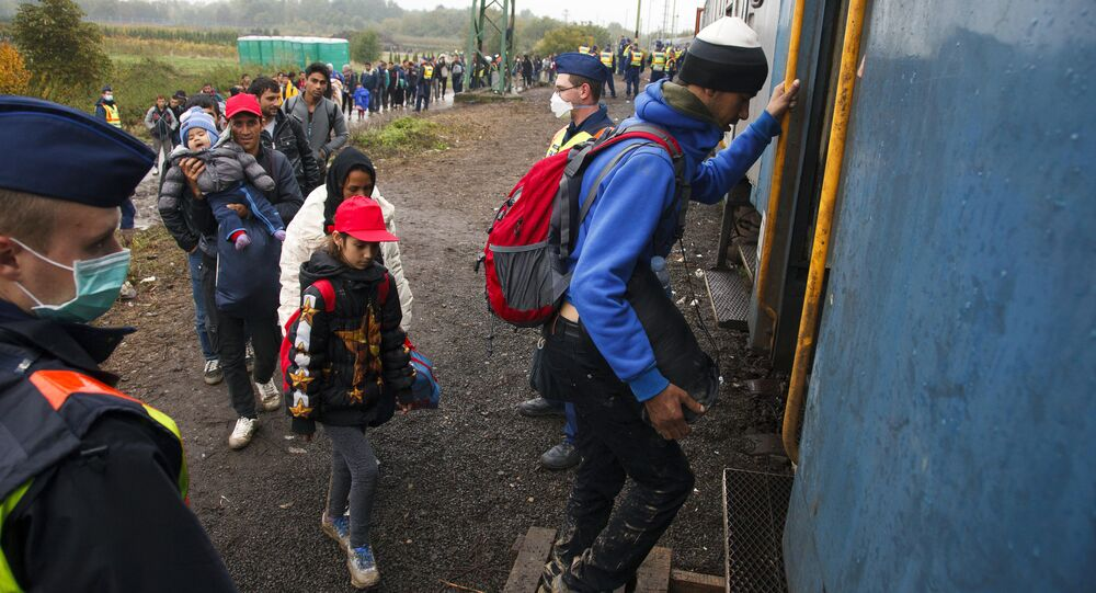 Migrants board a train after making their way through the countryside and crossing the Hungarian-Croatian border near the village of Zakany in Hungary to continue their trip to north on October 16, 2015