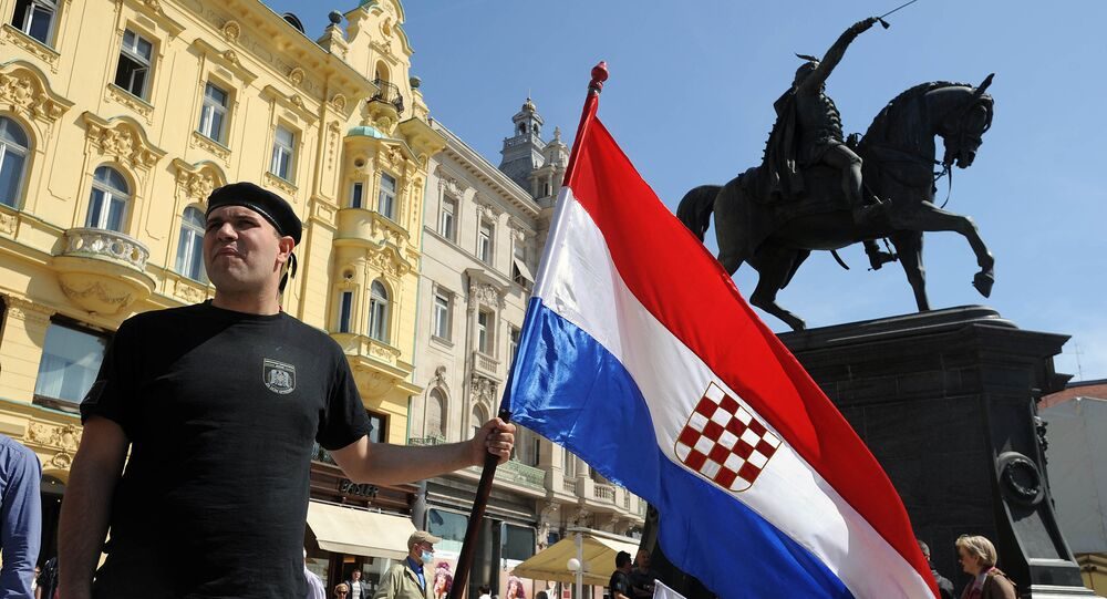 A man holds the Croatian flag as he takes part to a march in support of the Homeland War veterans' rights in Zagreb on April 14, 2015. Croatian leaders April 22, 2016, honoured the victims of the Balkan country's most notorious World War II death camp, in an event boycotted by critics who accuse rulers of tolerating a revival of pro-Nazi ideology