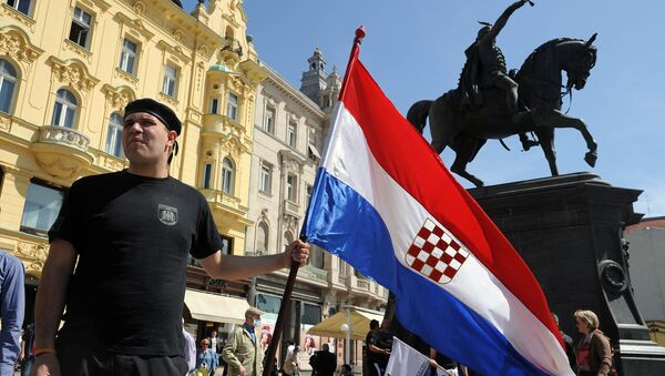 A man holds the Croatian flag as he takes part to a march in support of the Homeland War veterans' rights in Zagreb on April 14, 2015. Croatian leaders April 22, 2016, honoured the victims of the Balkan country's most notorious World War II death camp, in an event boycotted by critics who accuse rulers of tolerating a revival of pro-Nazi ideology - Sputnik International