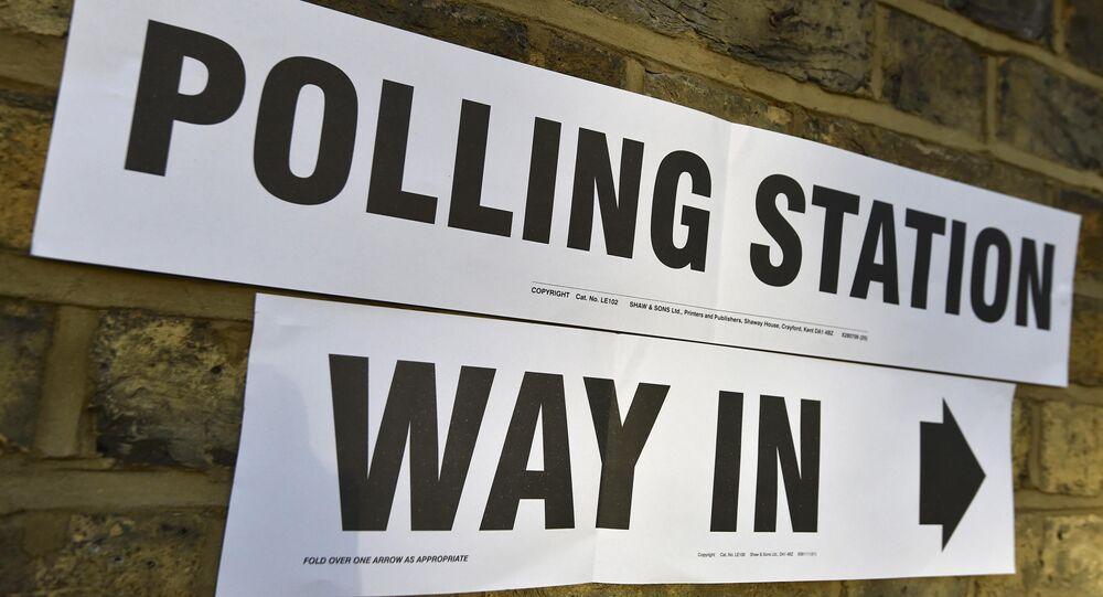 A sign on a wall points to the entrance of a polling station for the London mayoral elections, in west London, Britain May 5, 2016