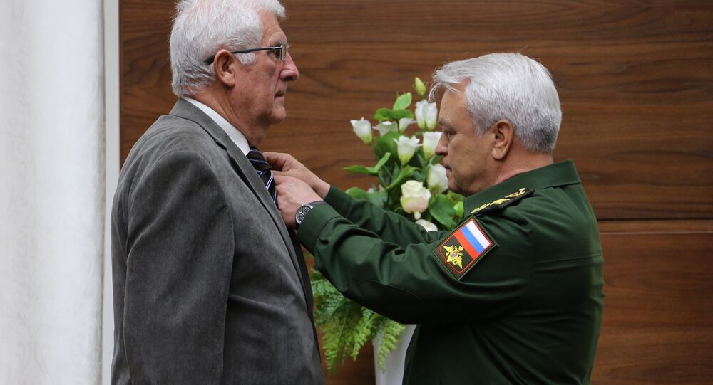 Jean-Claude Mague, left, a French citizen, during the presentation of his family military awards - the National Order of the Legion of Honor and the Military Cross - to the parents of Hero of Russia Alexander Prokhorenko, who was killed in Syria. The ceremony took place at the Russian Defense Ministry.