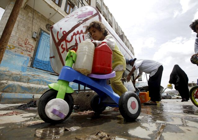 A girl transports jerrycans with clean water on her tricycle, after filling up from a donated source amid a shortage of water supply, in Yemen's capital Sanaa, April 14, 2016.