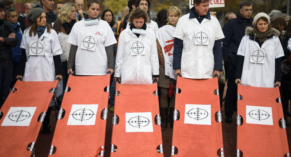 Staffs of Doctors Without Borders, also known by its French name Medecins Sans Frontieres (MSF), hold stretchers with a target on it during a demonstration on November 3, 2015 in Geneva.