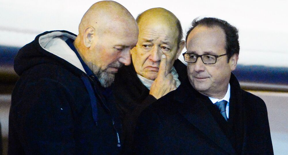 Serge Lazarevic (L), France's last remaining hostage, French President Francois Hollande (R) and French Defence Minister Jean-Yes Le Drian walk on the tarmac after Lazarevic landed in a French Republic plane at the Villacoublay military base near Paris on December 10, 2014