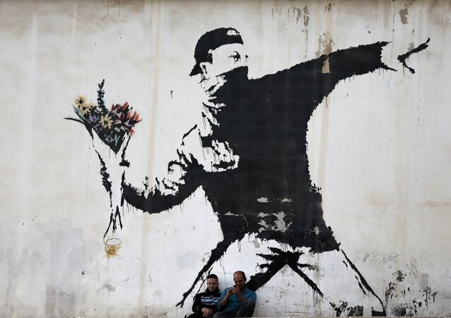 Two men are sitting in front of a famous graffiti of British street artist Banksy, painted on a wall of a gas station in the West Bank city of Bethlehem on December 16, 2015.