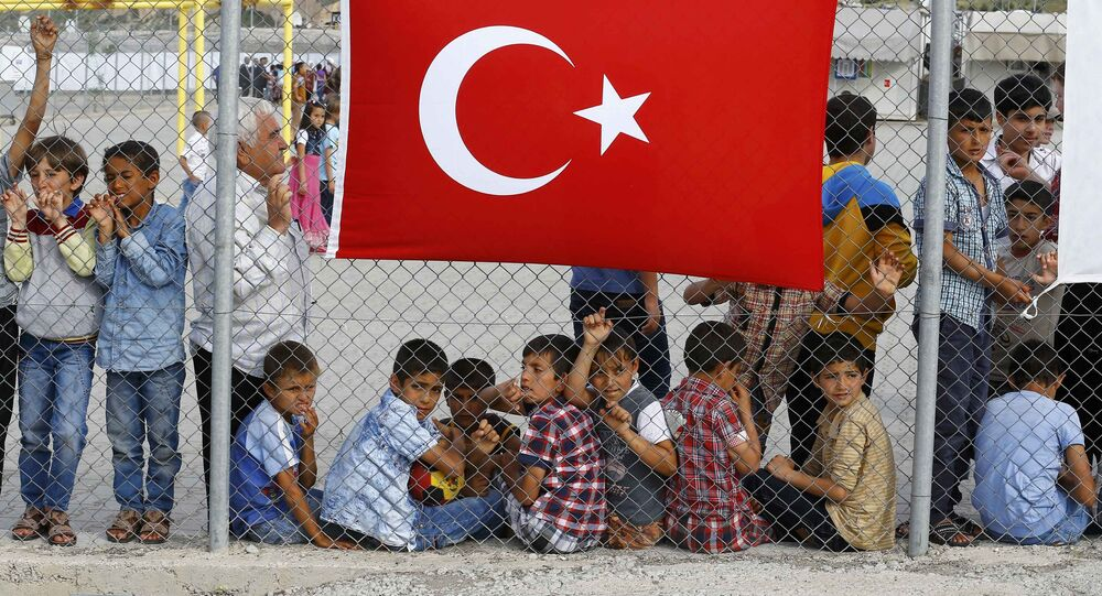 An elderly refugee man stands with children as they wait for the arrival of German Chancellor Angela Merkel, Turkish Prime Minister Ahmet Davutoglu, EU Council President Donald Tusk and European Commission Vice-President Frans Timmermans (all not pictured) at Nizip refugee camp near Gaziantep, Turkey, April 23, 2016.s