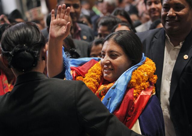 Bidhya Devi Bhandari of the Communist Party of Nepal Unified Marxist-Leninist waves her hand.