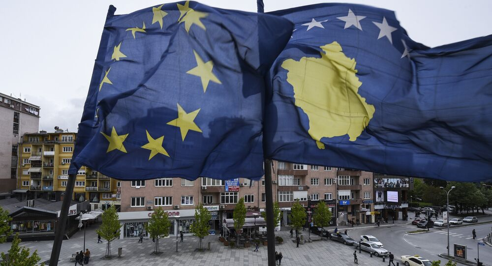 Kosovar Albanians walk under the EU and Kosovo flags in the main square of Pristina on May 4, 2016.