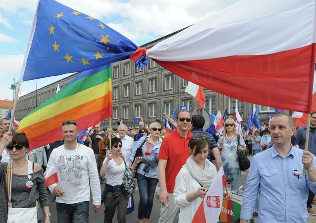 Opponents of Poland's government carry a Polish and EU flags tied together as they march downtown streets to protest the country's direction under a conservative government that is accused of eroding the rule of law, in Warsaw, Poland, Saturday, May 7, 2016.